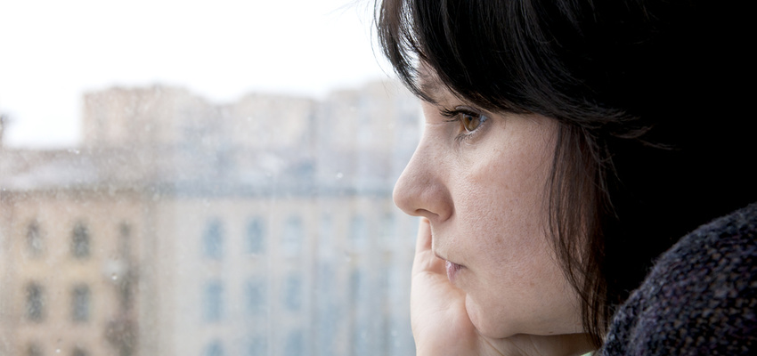 woman-looking-out-from-work-window-850x400